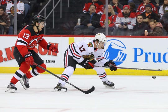 Jan 14, 2019; Newark, NJ, USA; Chicago Blackhawks center Dylan Strome (17) plays the puck while being defended by New Jersey Devils center Nico Hischier (13) during the first period at Prudential Center.