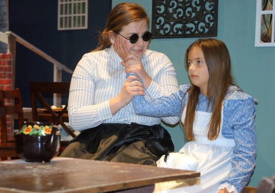Annie Sullivan (Taylor Benavidez) has Helen Keller (Carlie Maynes) feel the word she has just signed for the young deaf and blind child.