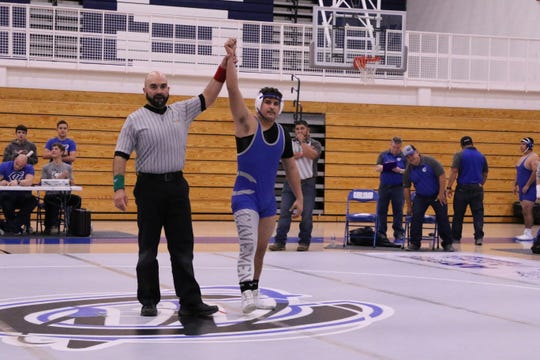 Carlsbad's RJ Baca has his hand raised after Roswell forfeited its match during Monday's District Dual.