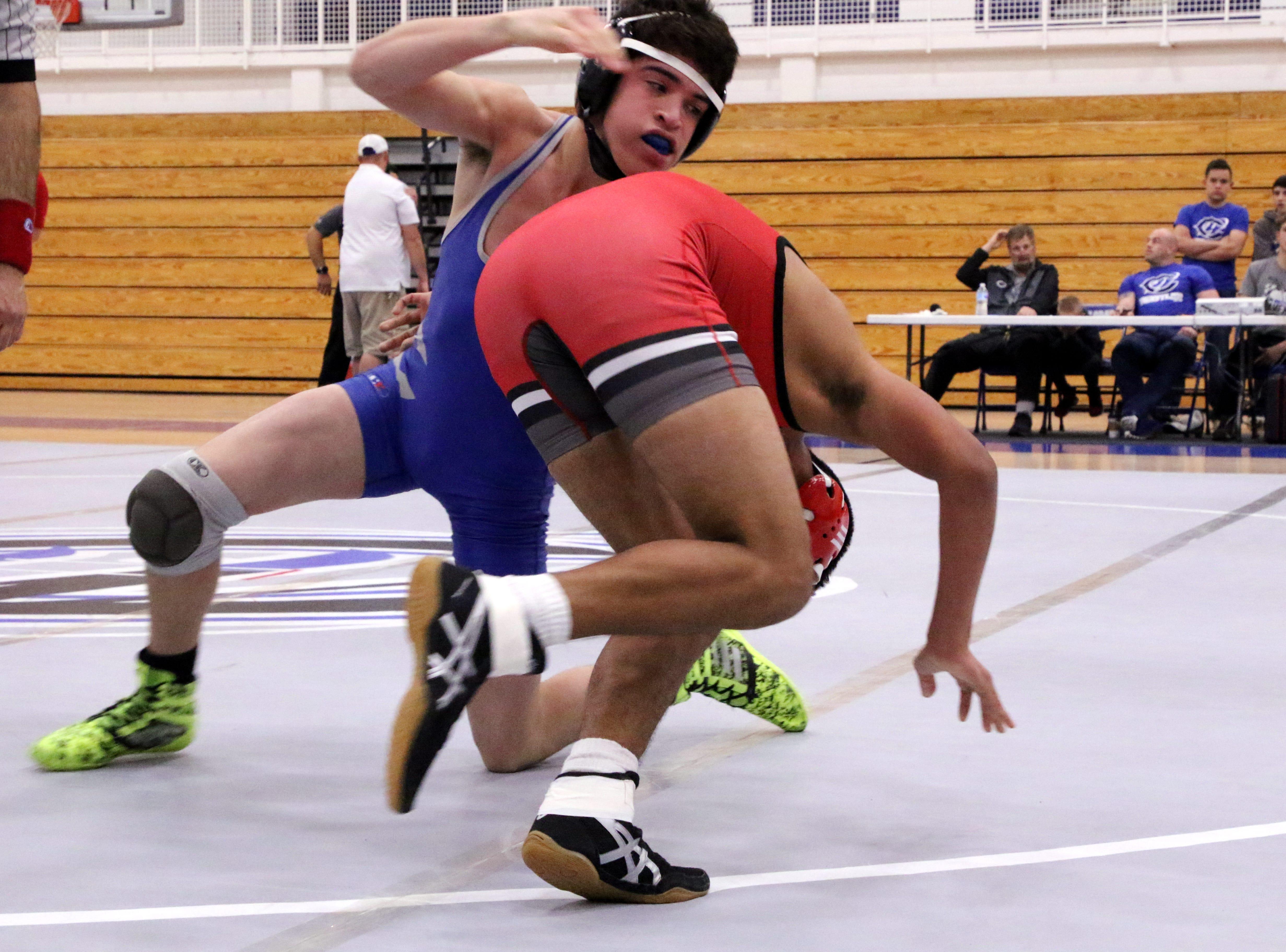 Carlsbad's Jesse Rodriguez drives Roswell's Estevan De la Fuente to the mat during Monday's District Dual.
