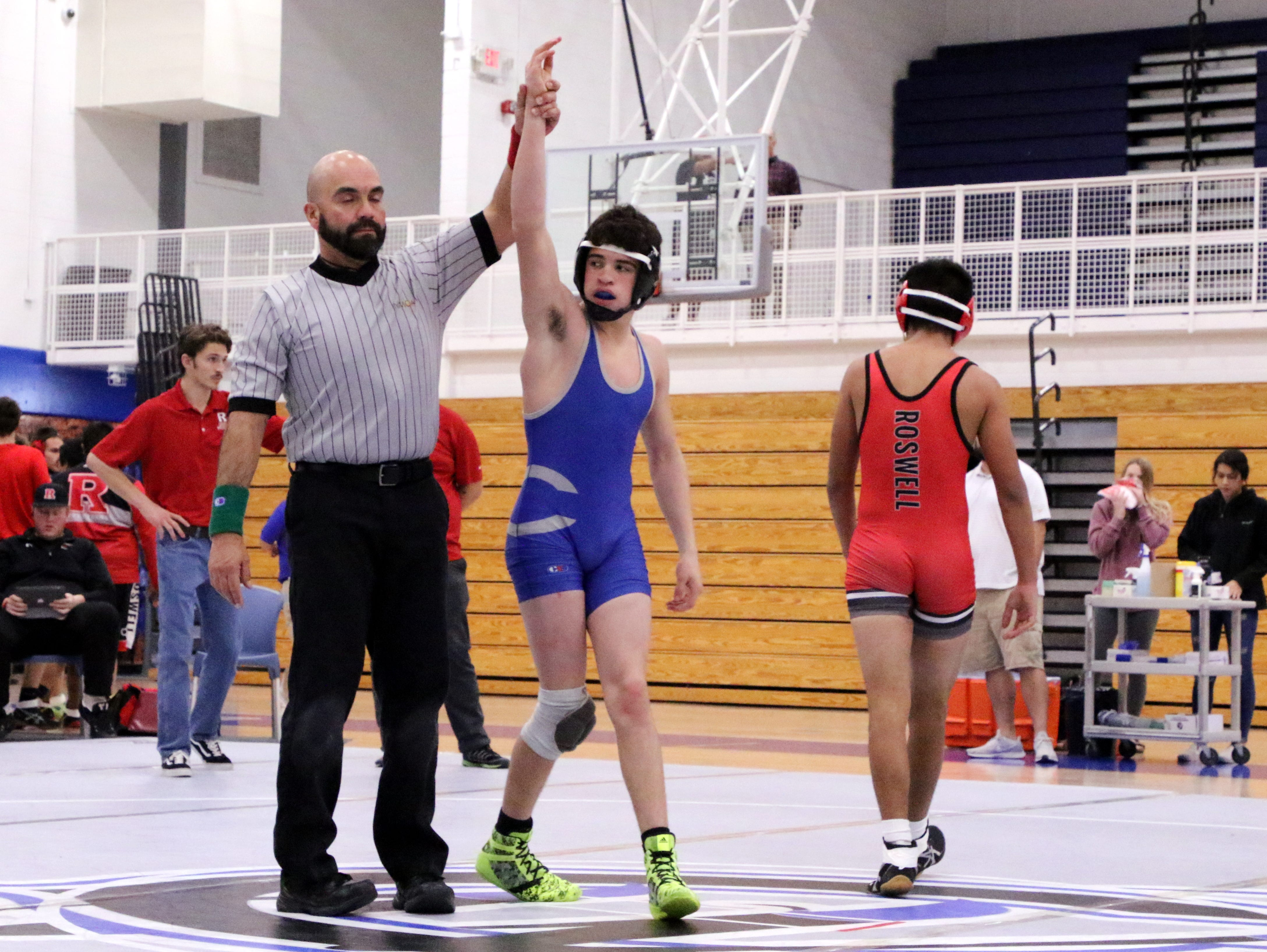 Carlsbad's Jesse Rodriguez has his hand raised after beating Roswell's Estevan De la Fuente via pinfall during Monday's District Dual.