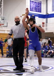 Fabian Padilla has his hand raised after beating Canaan Peralta via technical fall during Monday's District Dual against Roswell.