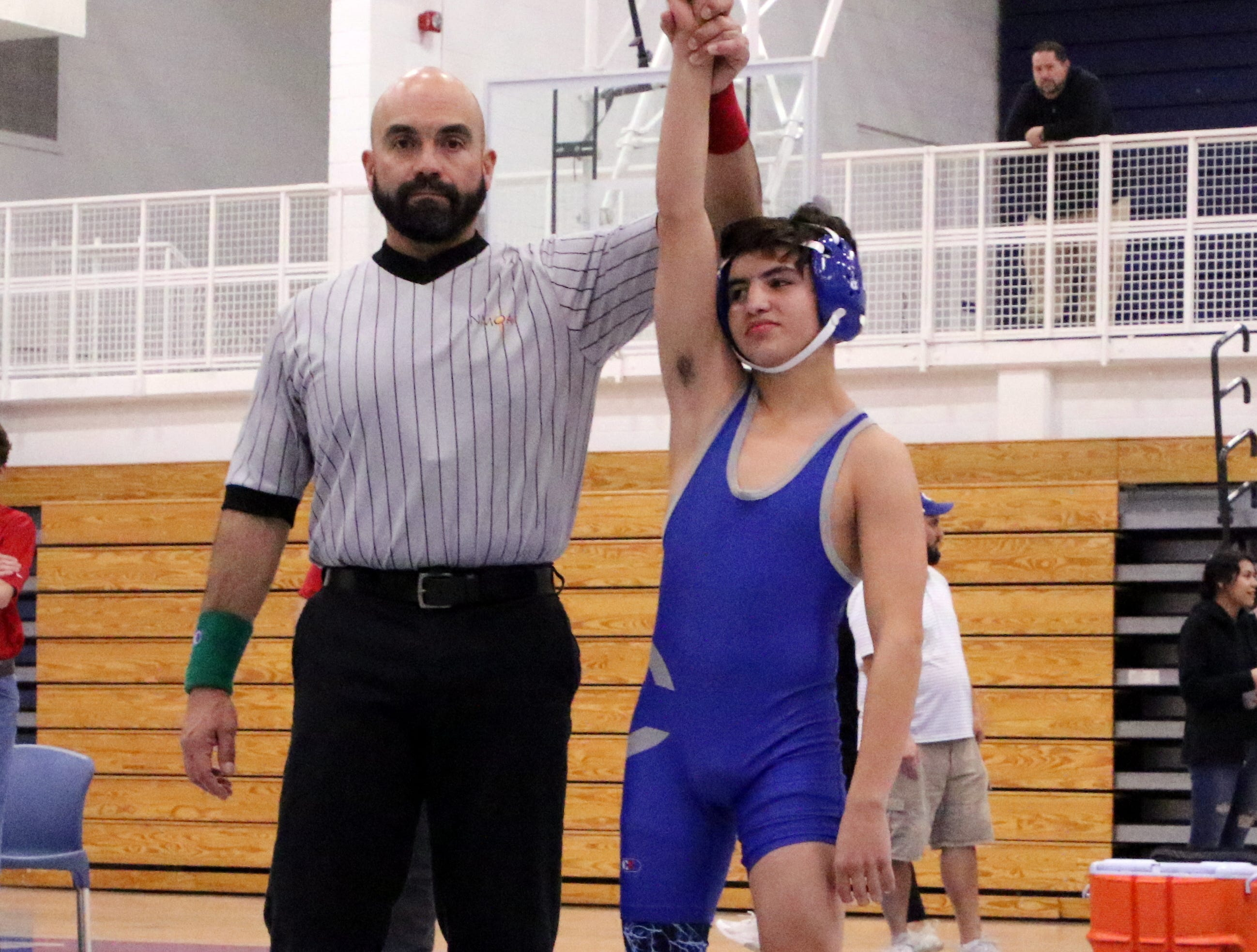 Carlsbad's Marcus Najera has his hand raised after Roswell forfeited its match during Monday's District Dual.