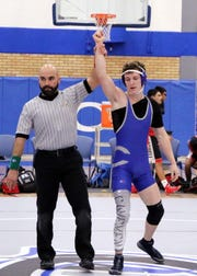Justin Wood has his hand raised after winning his match in 1:04 via pinfall during Monday's District Dual against Roswell.