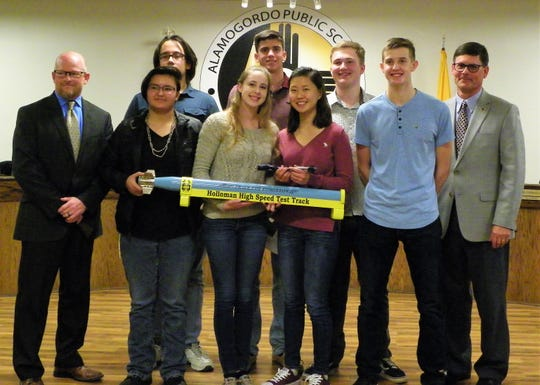 The Alamogordo High School Physics AP Shockwave team presented their project to the Alamogordo Public Schools Board of Education Dec. 12. To the left of the group is Interim Superintendent Jerrett Perry and to the right of the group is APS Board of Education President Timothy Wolfe.