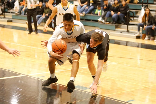 Navajo Prep's Treston Yazzie and Sandia Prep's David Gelb fight for possession of the ball during a Jan. 11 game  at the Eagles Nest in Farmington.