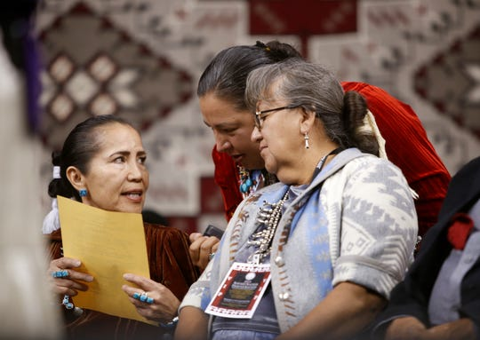Navajo Nation Chief Justice JoAnn B. Jayne, left, talks to Navajo Nation Council delegate Amber Kanazbah Crotty, center, during Tuesday's inauguration at the Bee Hółdzil Fighting Scouts Events Center in Fort Defiance, Ariz. Crotty was sworn-in for a second term on the tribal council.
