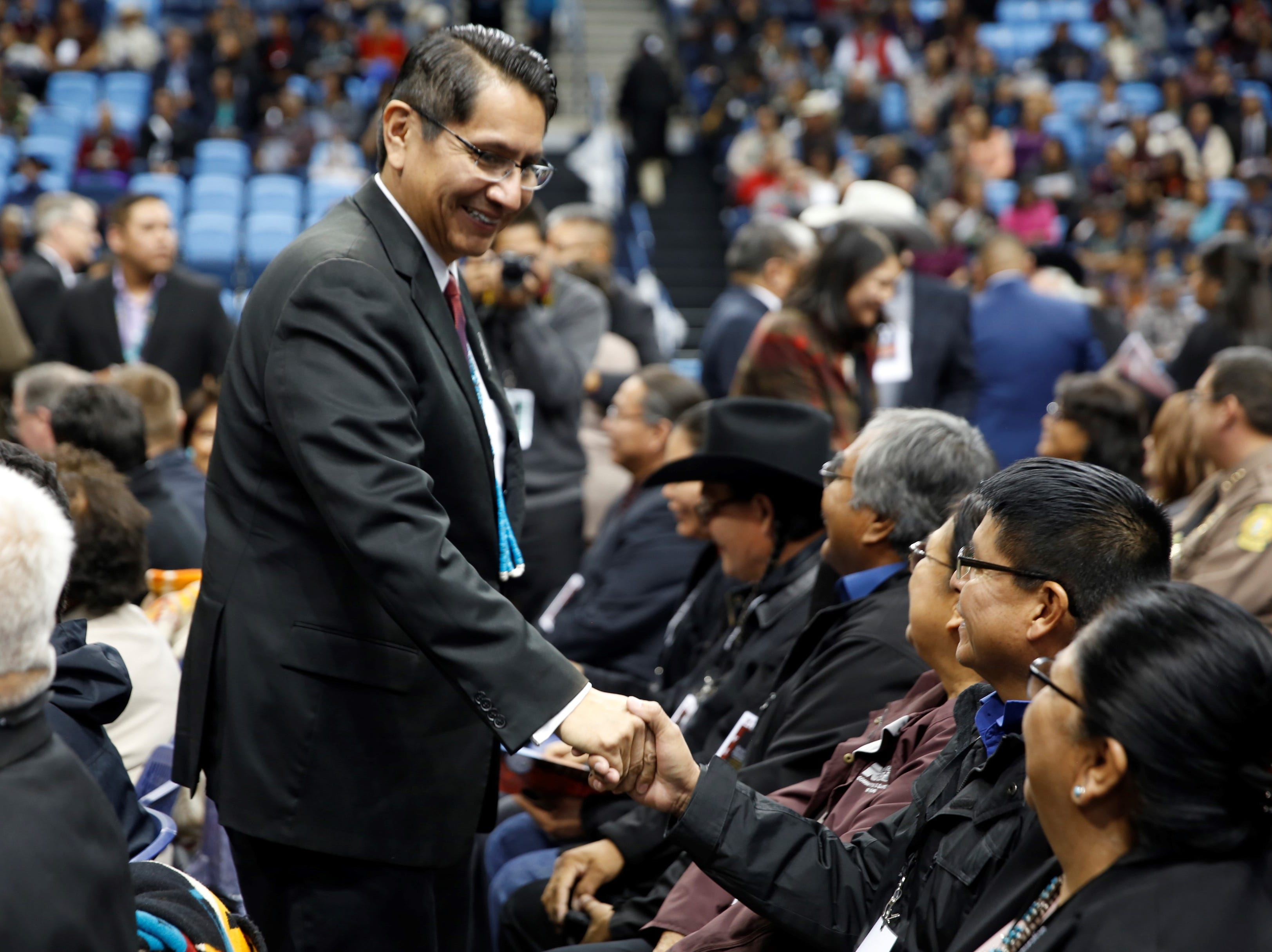 Jonathan Nez greets an attendee before the inaugural ceremony on Tuesday at the Bee Hółdzil Fighting Scouts Events Center in Fort Defiance, Ariz.