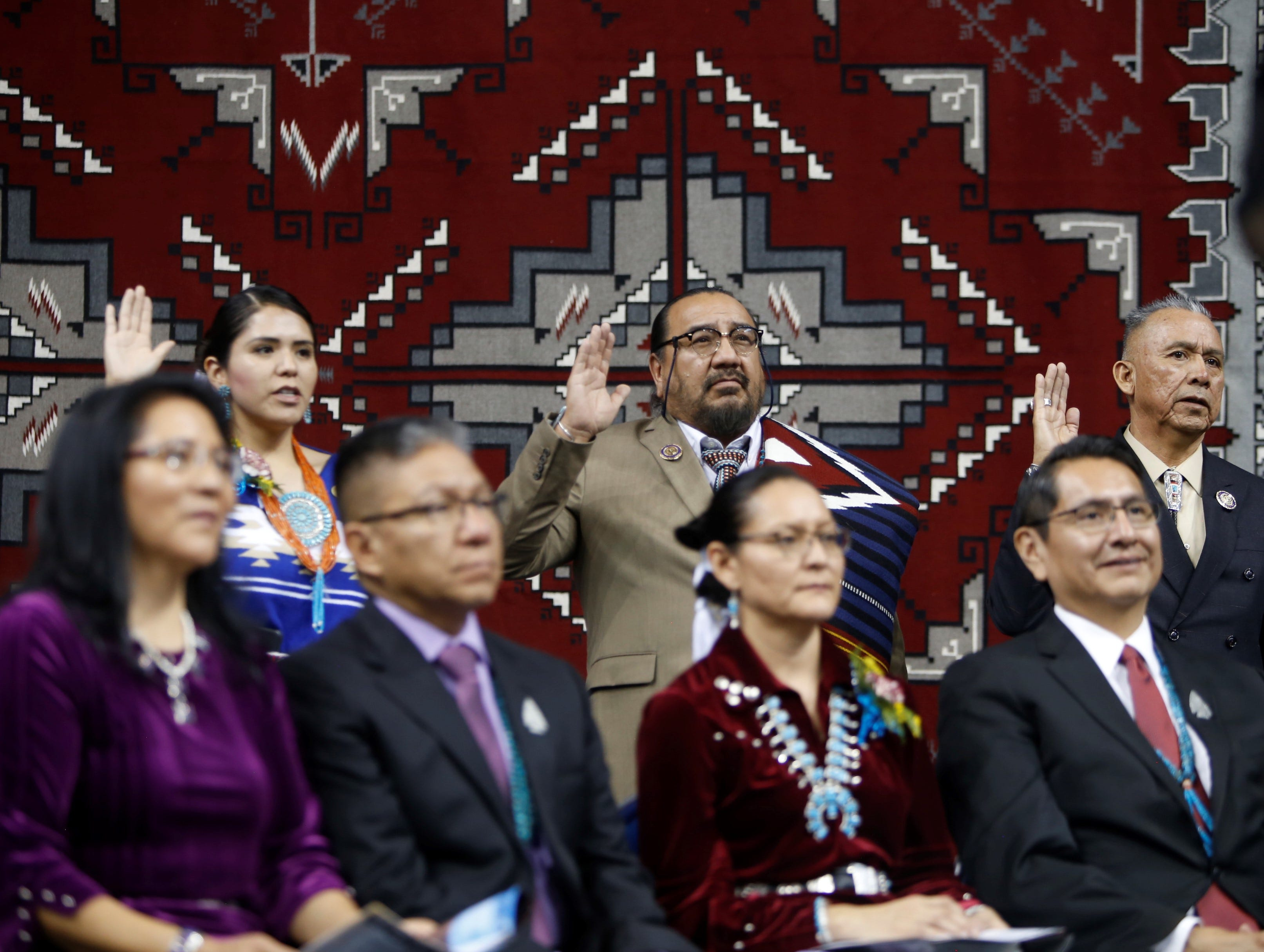 From left, Charlaine Tso, Raymond Smith Jr. and Rick Nez take the oath of office for the Navajo Nation Council during Tuesday's inauguration at the Bee Hółdzil Fighting Scouts Events Center in Fort Defiance, Ariz.