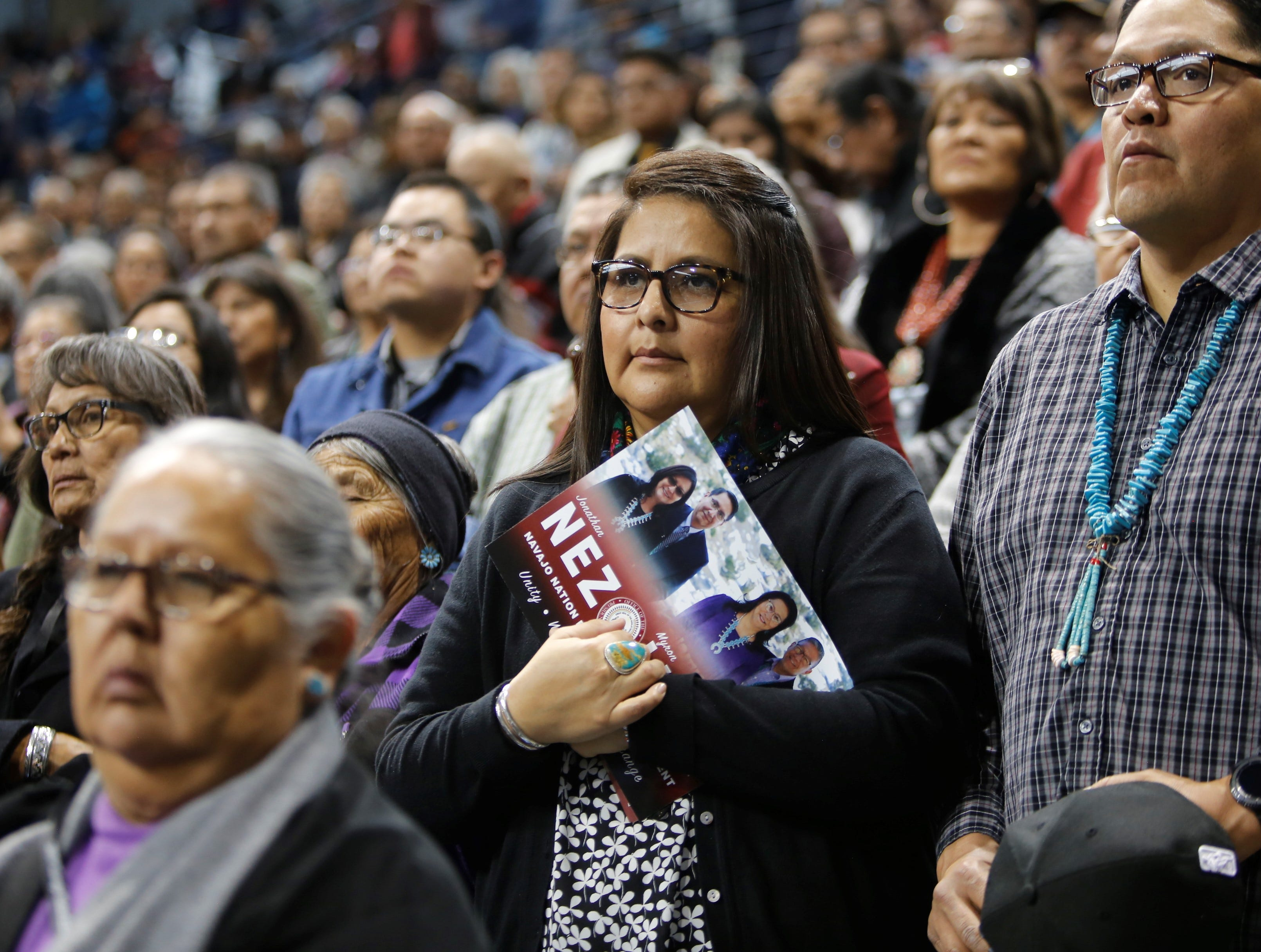 Charissa Benn, center, was among hundreds of tribal members who attended Tuesday's inauguration at the Bee Hółdzil Fighting Scouts Events Center in Fort Defiance, Ariz.