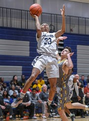 Demarko Coakley (23) goes in for two points over North Farmington defender Marshall Miller.