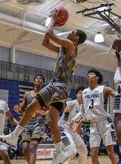 North Farmington's Justus Clark (with ball) attempts the shot against Farmington.