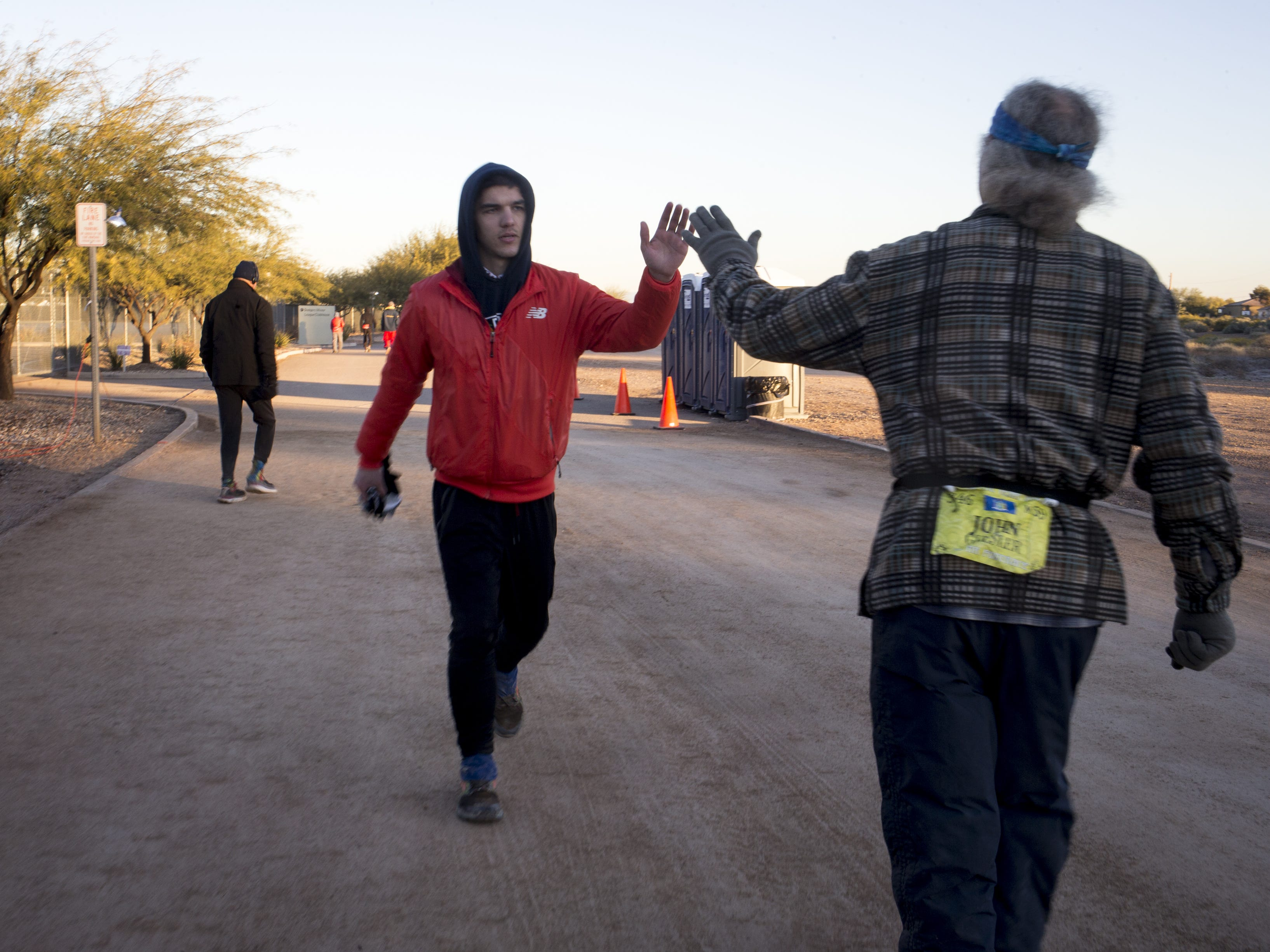 John Geesler (right) is high-fived by Gabriel Huseas (center), January 3, 2019, during the Across the Years Race at Camelback Ranch, 10710 W Camelback Road, Glendale. Geesler finished the six-day race with 395 laps/414 miles, placing him fifth.