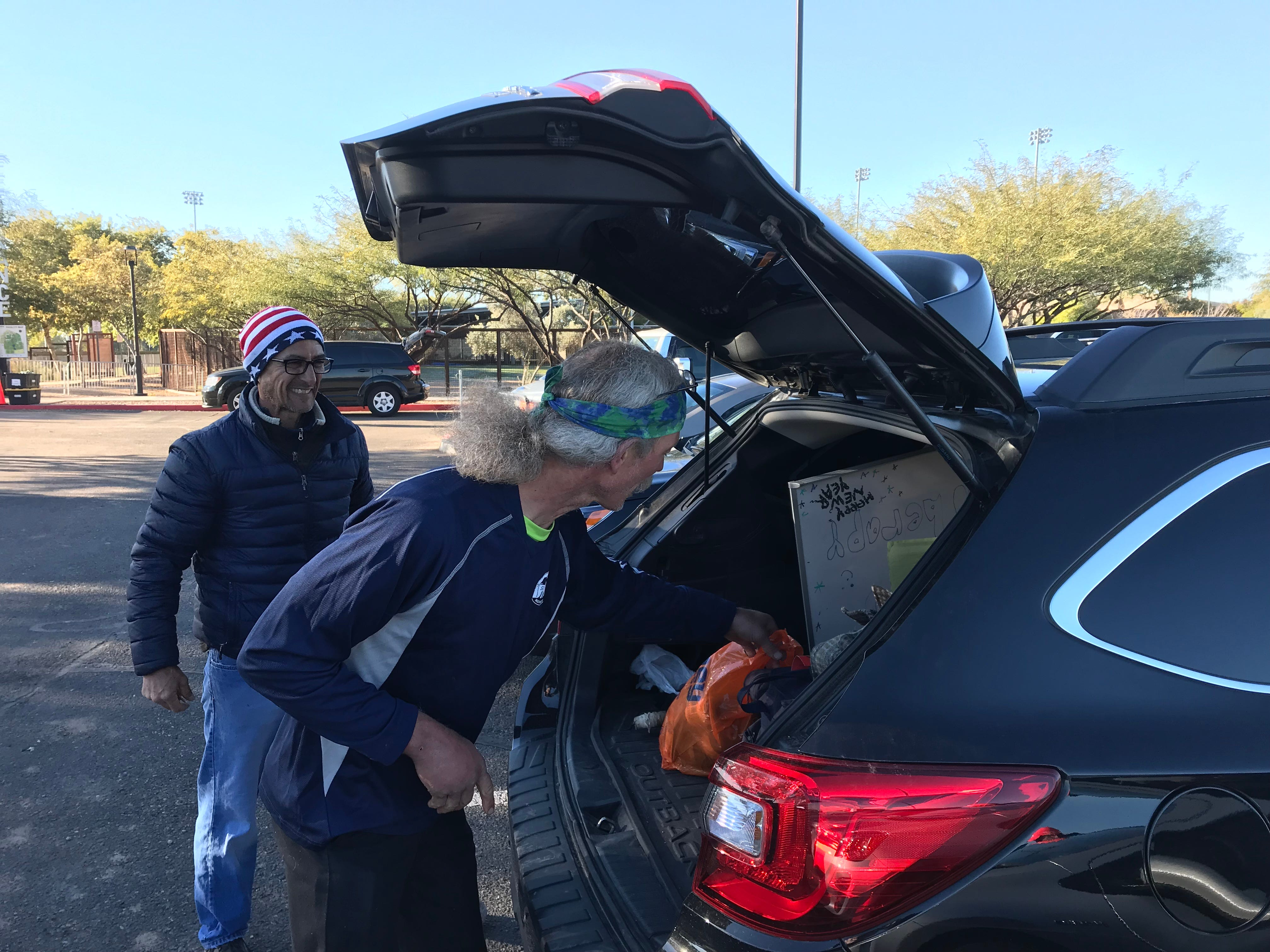 John Geesler (right) throws his bags in the car before he's driven to Sky Harbor International Airport. Despite running for 144 hours at the Across the Years Race at Camelback Ranch in Glendale, he had to be back at work the next day.