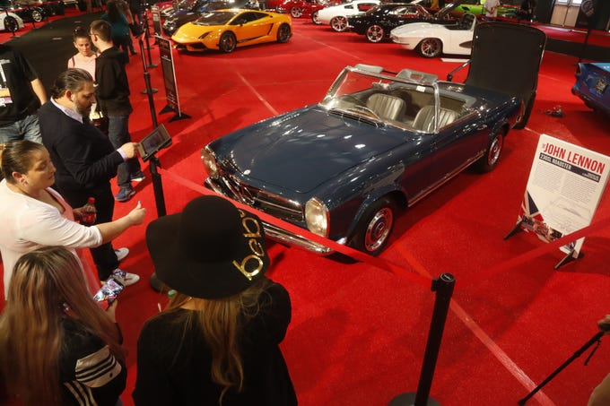 People gather around John Lennon's 1965 Mercedes-Benz 230SL Roadster at the Barrett-Jackson Car Auction in WestWorld in Scottsdale on Jan. 14, 2019.