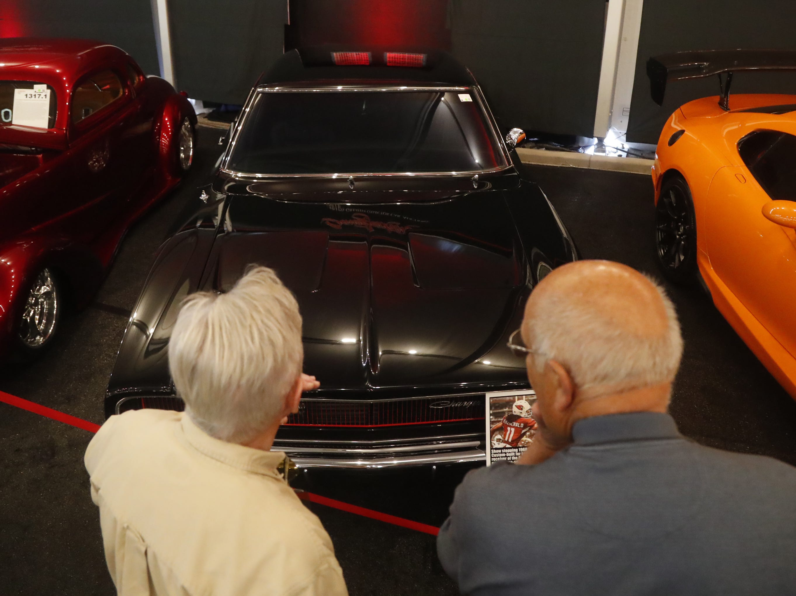 People look over Larry Fitzgerald's 1968 Dodge Charger R/T at the Barrett-Jackson Car Auction in WestWorld in Scottsdale on Jan. 14, 2019.