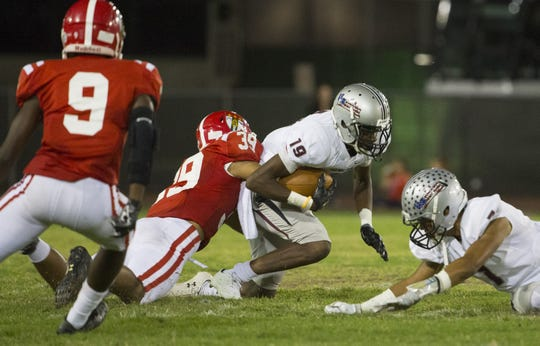 Brophy Prep's Marques White (39) tackles Hamilton's CJ Jarmon (19) at Phoenix Community College on September 30, 2016 in Phoenix, Ariz.