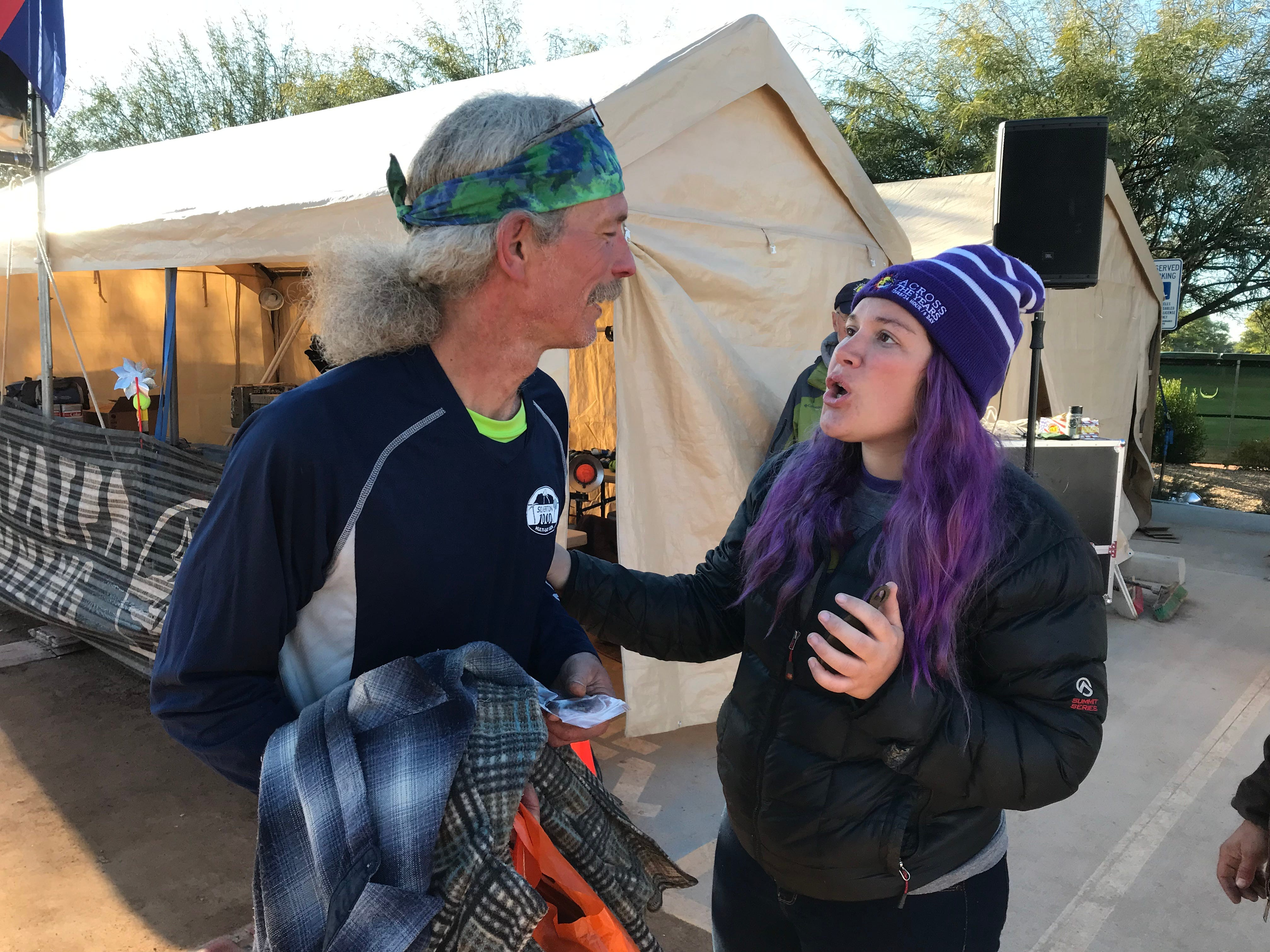 Jubilee Paige (right), director of the Across the Years Race at Camelback Ranch, Glendale, congratulates John Geesler on his finish.