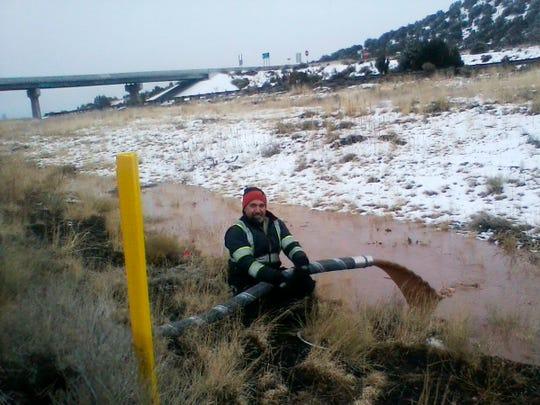 En esta foto proporcionada por el DPS se observa a uno de sus trabajadores vertiendo el chocolate líquido hacia un lado de la carretera.
