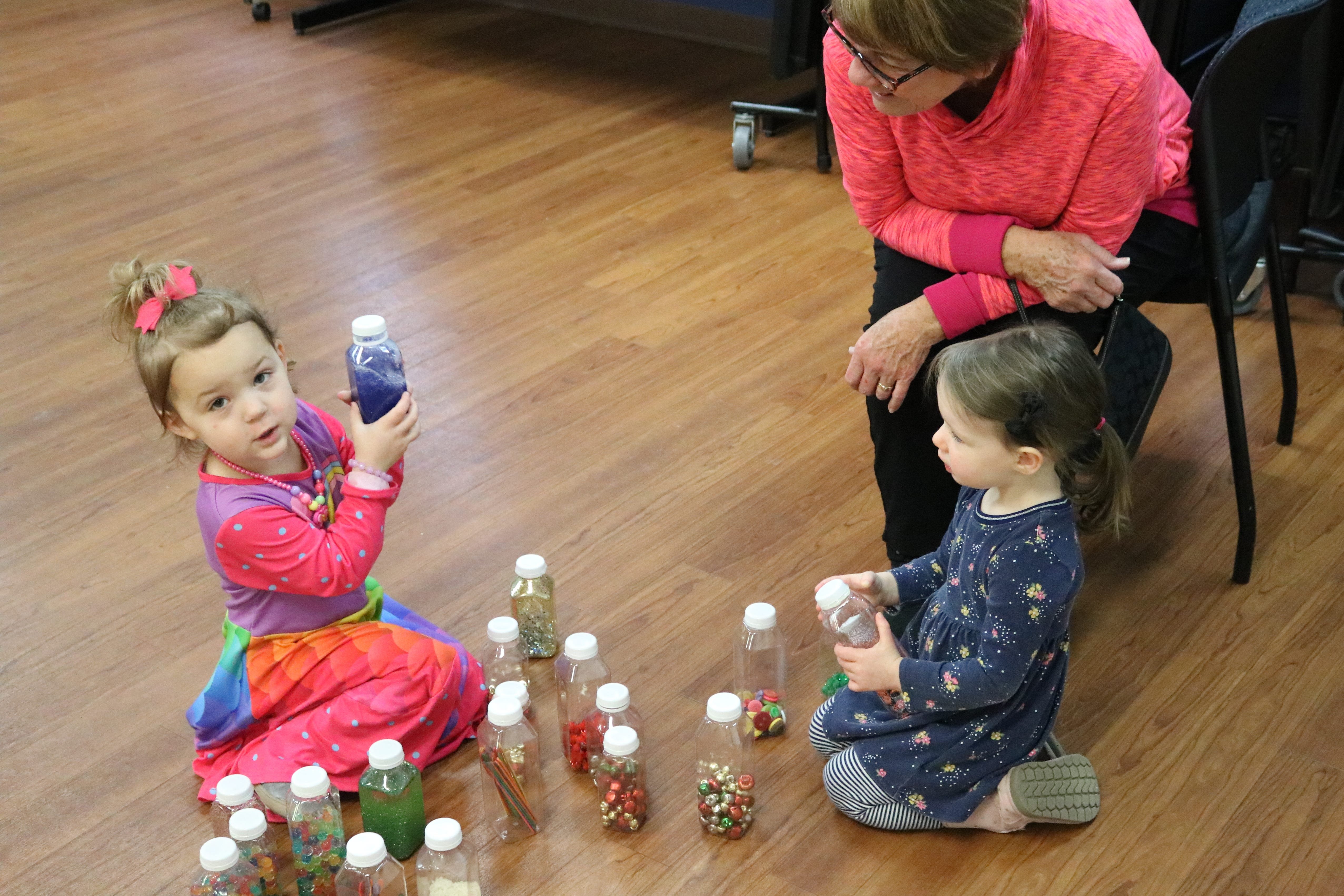 "Madelynn Meisler, 3, and Lindsay Dunn, 2, play with some homemade noisemakers during the ""Sensory Story Time"" program at Ida Rupp Public Library in Port Clinton on Tuesday."