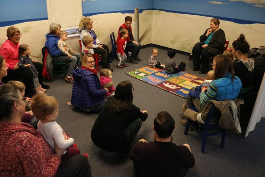 "Jennifer Buch, top right, leads a group of children and their families in song during the ""Sensory Story Time"" program at Ida Rupp Public Library in Port Clinton on Tuesday."