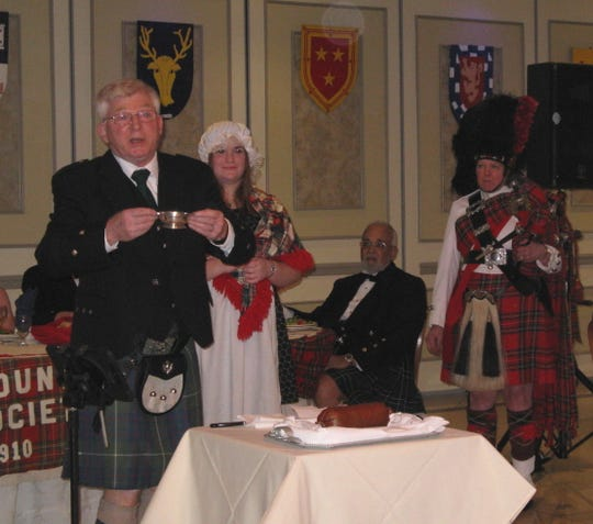 Smyth Graham of the Dutchess County Scottish Society, left to right, addresses the haggis during a past event with Lilly Campbell, Dan Jones and Janet Whalen, Pipe Major for The Amerscot Pipe Band.