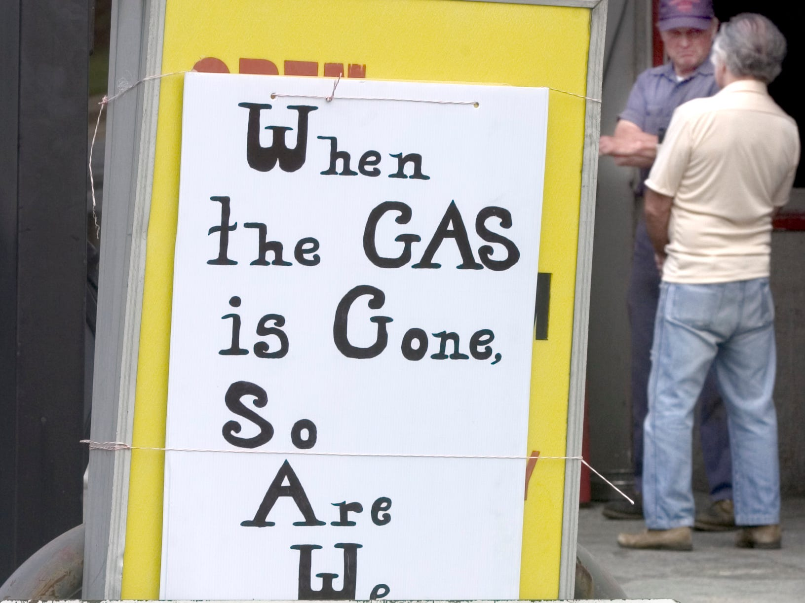 Lynn Haines talks with Ed Weigle, a longtime Lincoln Highway Garage customer. People still milled around the pumps even with the final closing sign in view on May 11, 2004.
