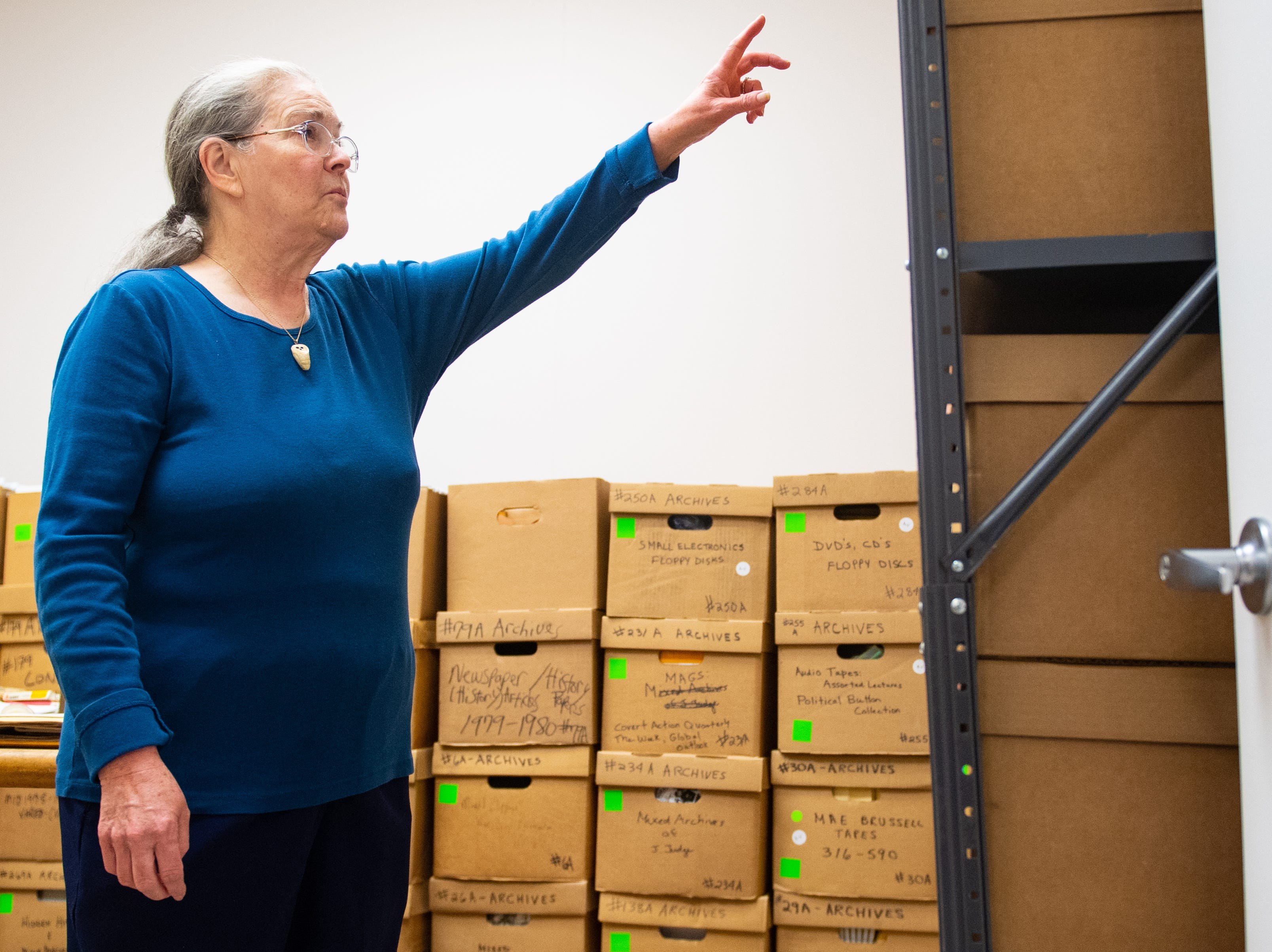 Marilyn Tenenoff reads the label on each box looking for a specific event in history at the national Hidden History Museum and Research Center, January 12, 2019.