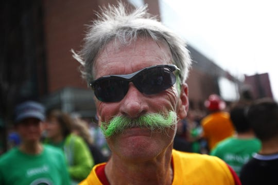 Jerry Roberts of Irondequoit dyed his long mustache green for the  Johnny's Runnin' of the Green 5-Mile race in 2012. The event is a community party as well as sporting event.