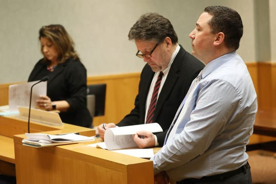 Suspended Rochester Police Officer, Michael Sippel listens to Rochester City Court Judge, Thomas Rainbow Morse, issues his decision not to dismiss the case against him while his attorney, Clark Zimmermann, looks over the ruling.