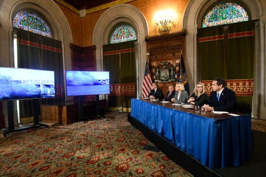 New York Gov. Andrew Cuomo, right,  watches from the Red Room in the state Capitol as the east anchor span of the old Tappan Zee Bridge is imploded by contractors Tuesday, Jan. 15, 2019, in Albany, N.Y.