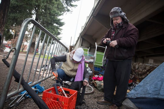Dan Sheets, a volunteer who would serve the homeless under the Marion Street Bridge, and Becky Attenberger gather tools and other items left behind under the Marion Street Bridge move out on Tuesday, Jan. 15, 2019. After the city cleared out those living under the bridge, some left belongings behind.
