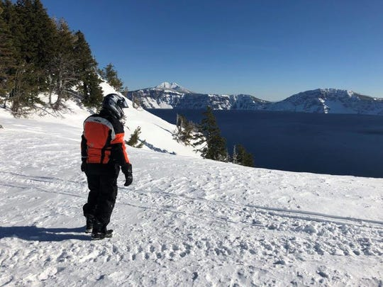 Steve Roe of Grants Pass looks out at Crater Lake after snowmobiling to the rim.