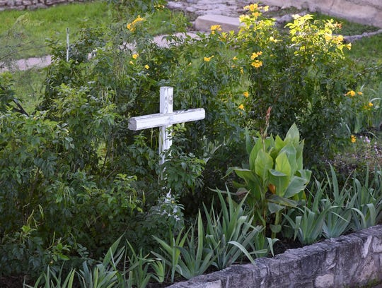 A cross sits amidst blooms in the sunken garden of St. Paul Presbyterian Church, 11 N. Park St. in San Angelo.