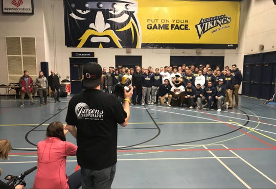 Members of the Minnesota Twins take a picture with the national-champion Augustana University baseball team.