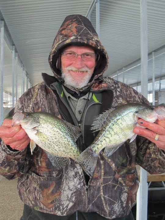 Dennis Hymer, Strafford, with a couple of winter crappie he caught while fishing off a dock.
