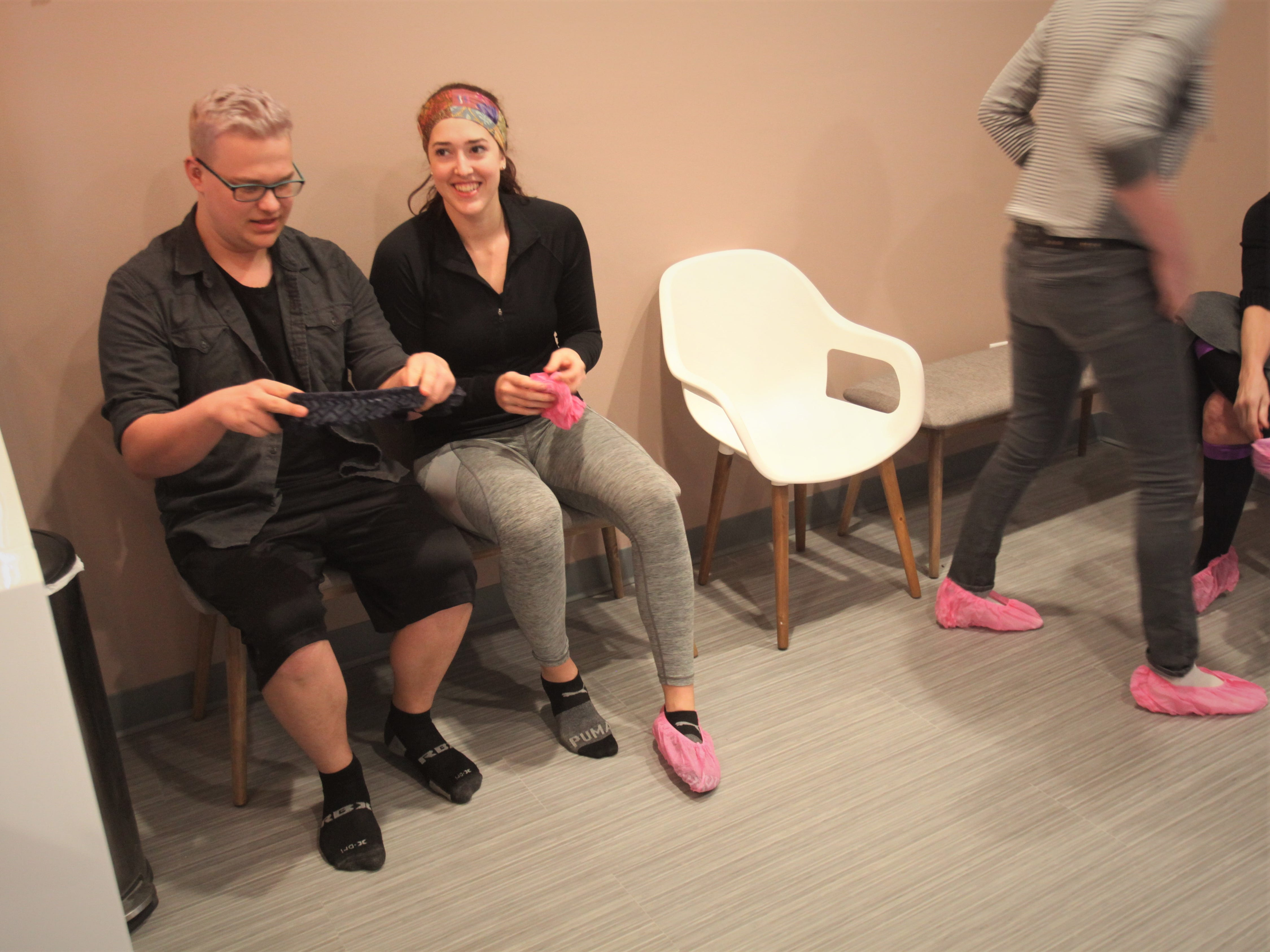 Mason Gold and Evangeline Leuchen put on booties over their socks before a salt therapy session.