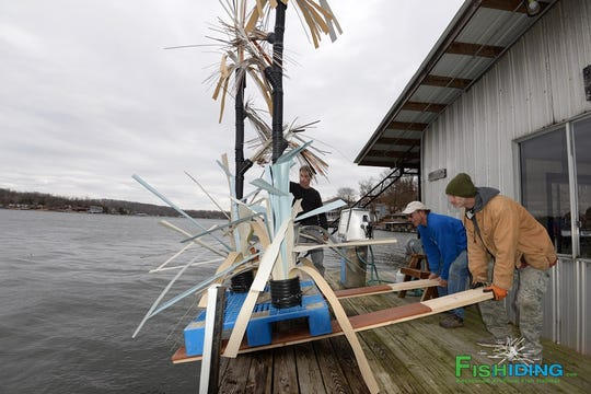 Fishiding.com company workers prepare to slide a tall fish habitat structure into the water next to a dock at Point View Resort at Lake of the Ozarks.