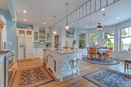 A large island sits in the center of the kitchen, allowing for easy preparation while visiting with guests.