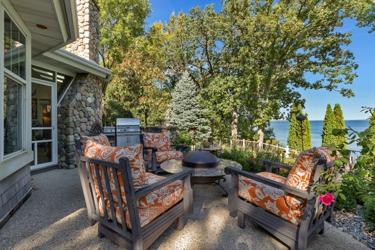 A large ground-level deck sits at the back of the house complete with an outdoor fieldstone fireplace.