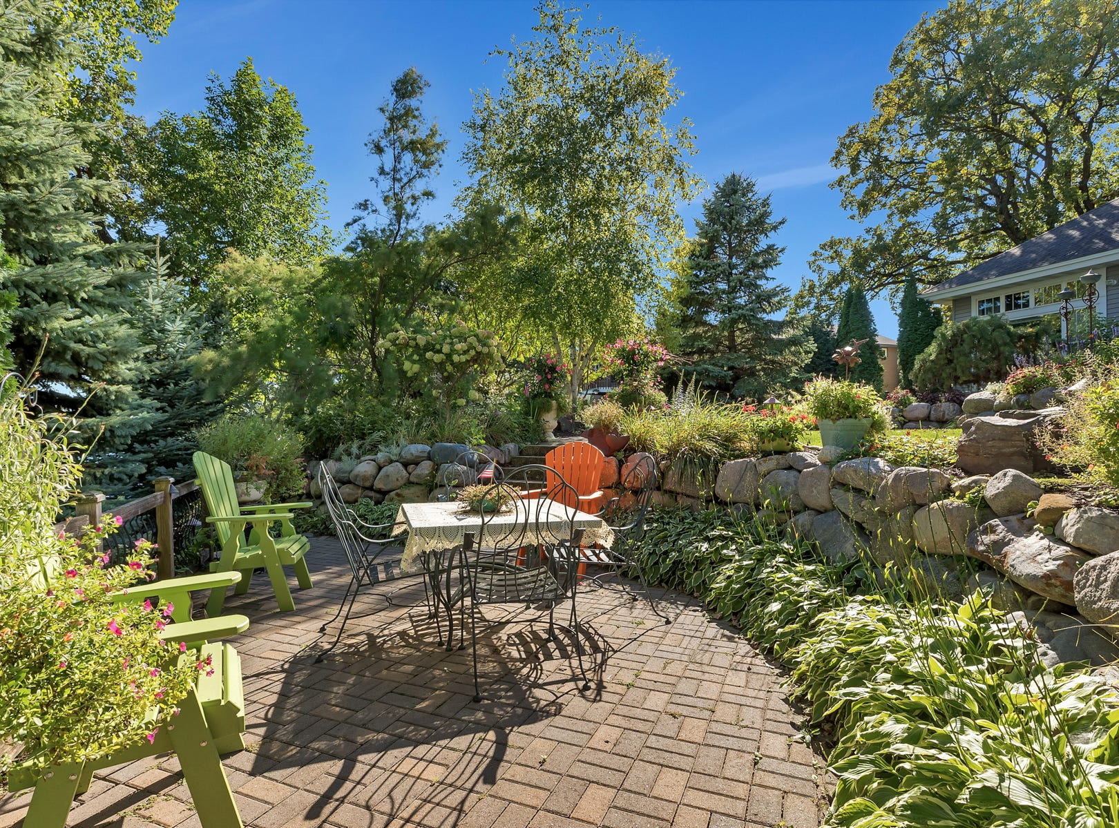 Nearby stairs lead down to a paver walkway and patio surrounded by lush green plantings and stunning views of the lake.