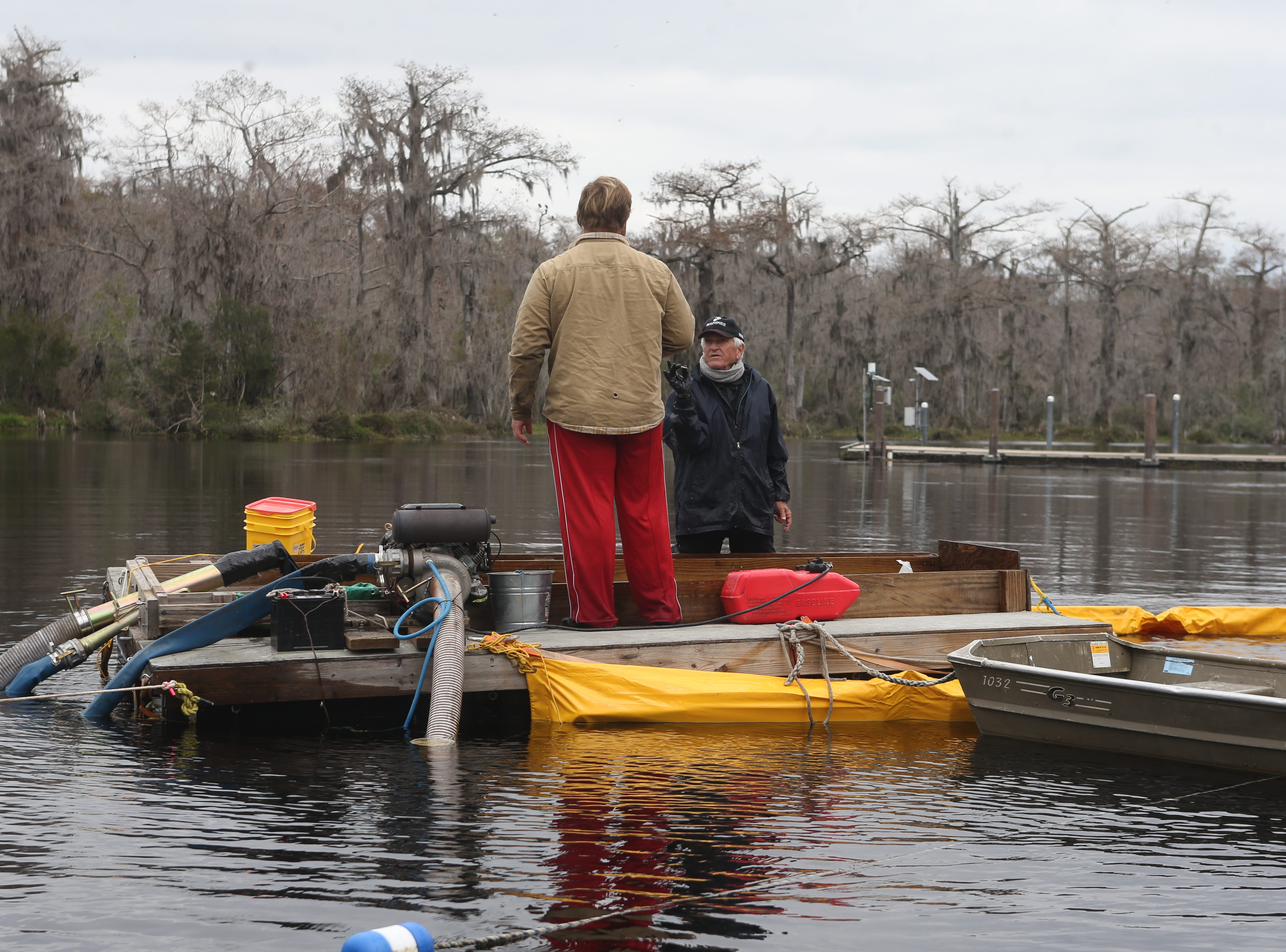 Binghamtom University masters student and volunteer Gavin Donathan, left and volunteer screener Ken Beattie look at an arrowhead brought up from the bottom of the Wakulla River by a dredge as researchers scuba dive to the bottom to observe the remains of a mastodon Monday, Jan. 14, 2019.