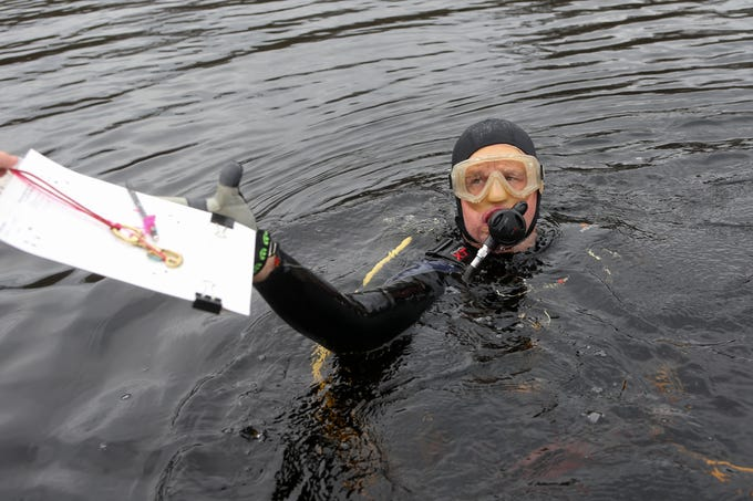 Co-principal Investigator Andy Hemmings grabs his waterproof clipboard before he scuba dives to the bottom of the Wakulla River to observe the remains of a mastodon Monday, Jan. 14, 2019.