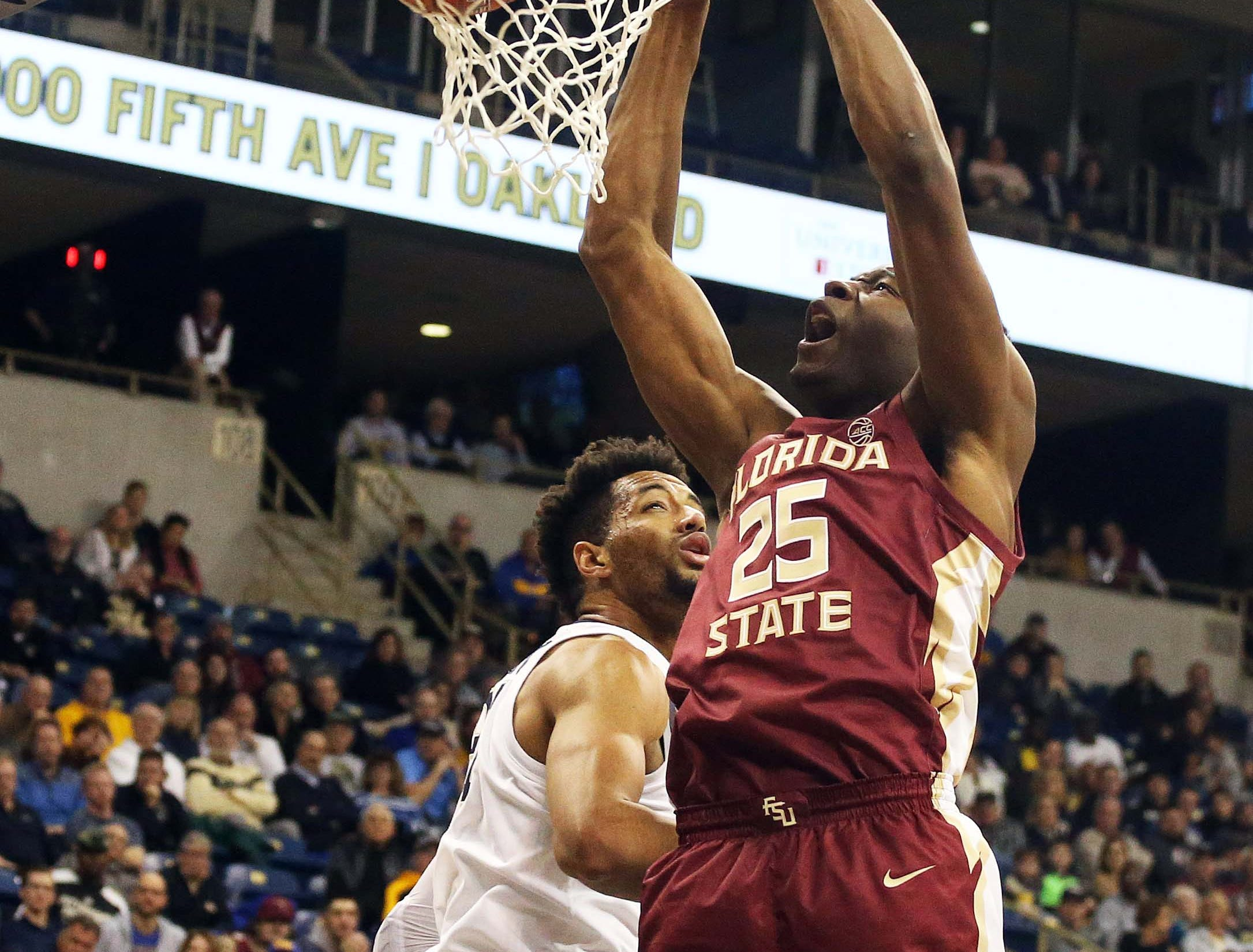 Jan 14, 2019; Pittsburgh, PA, USA; Florida State Seminoles forward Mfiondu Kabengele (25) dunks past Pittsburgh Panthers forward Terrell Brown (21) during the second half at the Petersen Events Center. Pittsburgh won 75-62. Mandatory Credit: Charles LeClaire-USA TODAY Sports