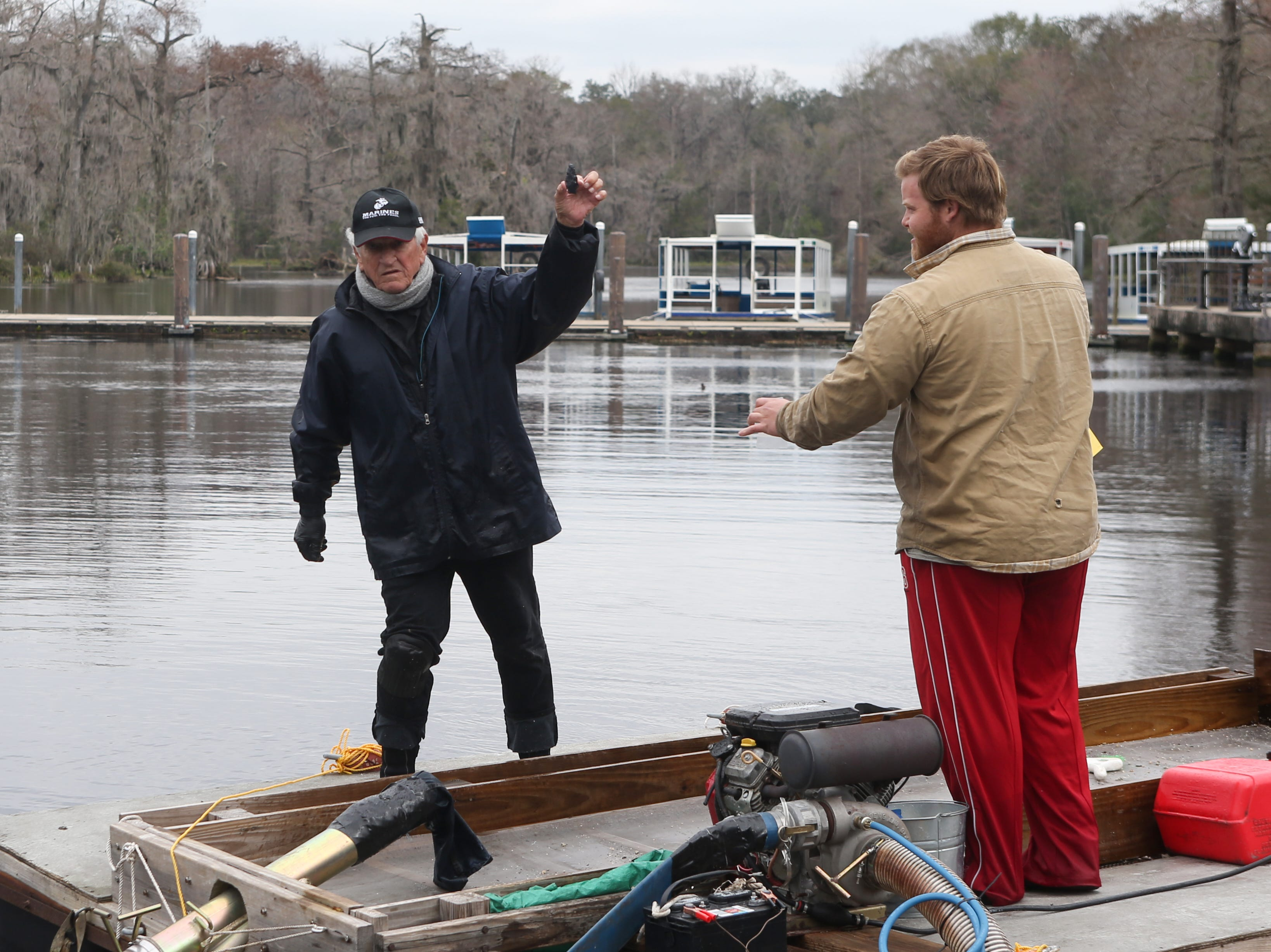 Volunteer Ken Beattie holds up an arrowhead he found in the water dredged up from the bottom of the Wakulla River as researchers scuba dive down eight feet to observe the remains of a mastodon there Monday, Jan. 14, 2019.
