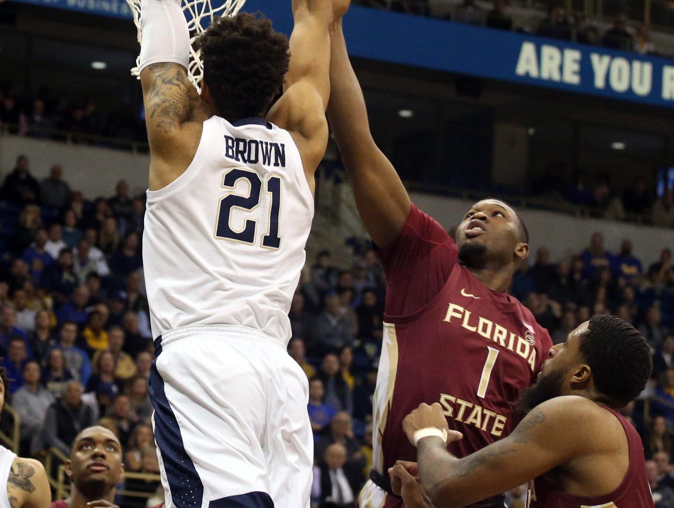 Jan 14, 2019; Pittsburgh, PA, USA; Pittsburgh Panthers forward Terrell Brown (21) dunks against Florida State Seminoles forward Raiquan Gray (1) during the second half at the Petersen Events Center. Pittsburgh won 75-62. Mandatory Credit: Charles LeClaire-USA TODAY Sports