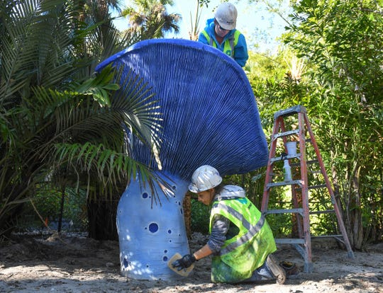 "Crystal Ploszay (top), owner of Unicorn Epoxy, of Vero Beach, and her crew member Jessica Hanson, working in collaboration with Scenario of Orlando, paint the details on one of fourteen lactarius indigo mushrooms on Tuesday, Jan. 15, 2019, for the new Children's Garden being constructed in the north side of McKee Botanical Garden in Indian River County. ""It's something our community has been needing, a little getaway destination for the kids to use their imaginations, and go to a whole new world,"" Ploszay said."