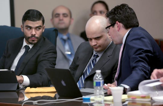 Reputed Kinfolk biker gang member Javier Gonzalez, center, talks to his attorneys during his murder trial in El Paso.