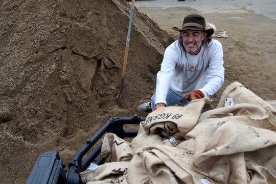 Mike Reisbord, who has a home in the Broad Beach neighborhood of Malibu, collects sandbags at Zuma Beach on Tuesday as the storm brought evacuation warnings to areas affected by the recent Woolsey Fire.
