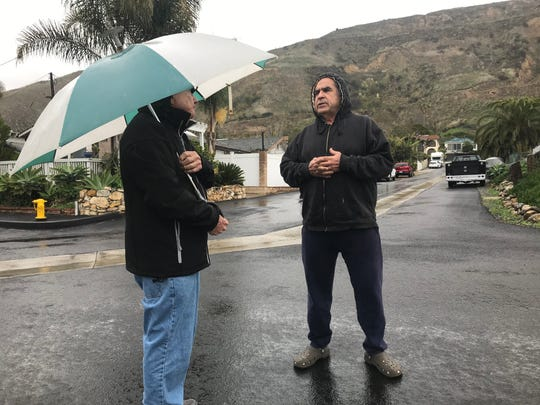 Bob Hart (left) talks with Michael Chavez Tuesday morning in La Conchita as the area gets ready for the second of a series of storms headed into Ventura County.